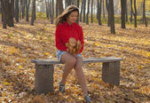 Girl sitting on a bench in autumn park. — Stock Photo