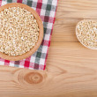Stock Photo: Buckwheat in bowl on wooden table.