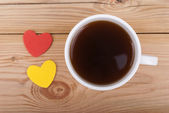 Cup of coffee and two hearts on a wooden background. — Stock Photo