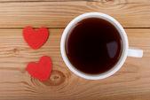 чашка кофе и два сердца на фоне деревянной. — Стоковое фото
