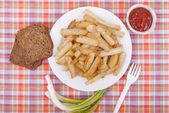 Fried potatoes in a plate on a tablecloth. — Stock Photo
