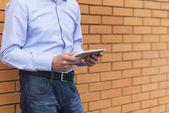 Cerca de las manos del hombre de negocios con un tablet pc. al aire libre — Foto de Stock