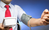 Businessman with blood pressure cuff on arm — Stock Photo