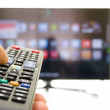 Smart tv and hand pressing remote control — Stock Photo #45739893