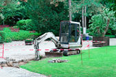 Small excavator working in the park — Stock Photo