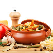 Pasta and spices in a ceramic pot — Stock Photo