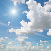 Sun on blue sky with white clouds — Stock Photo