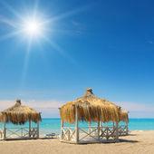 Beach, bungalows, blue sky and sun — Stock Photo