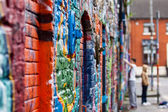 Graffiti wall with painters — Stock Photo