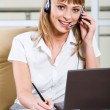 A young business woman sitting in headset at the laptop — Stock Photo #10710414