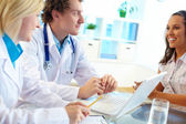 Clinicians consulting female — Stock Photo