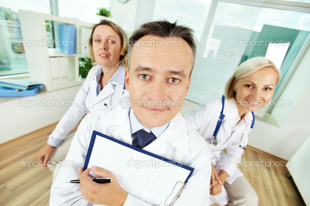 Portrait of male clinician with clipboard and his two colleagues looking at camera in hospital — Stock Photo #13723448