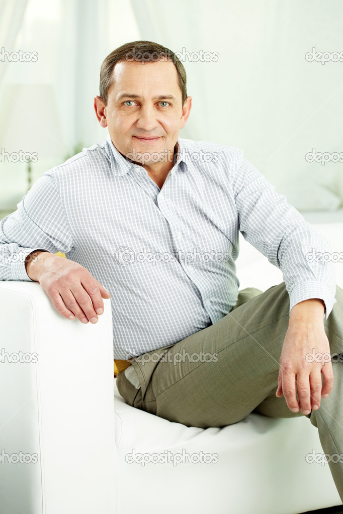 Portrait of mature man sitting on sofa and looking at camera — Stock Photo #13723587