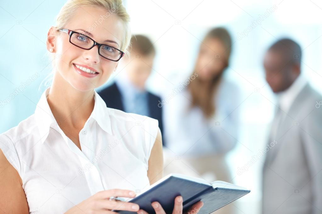 Portrait of busy secretary with notepad looking at camera in working environment — Stock Photo #13723810