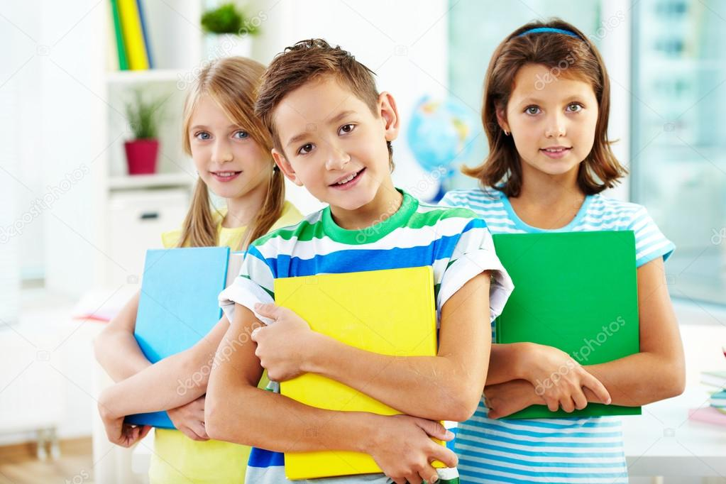 Portrait of happy classmates with books looking at camera in classroom — Stock Photo #13723929
