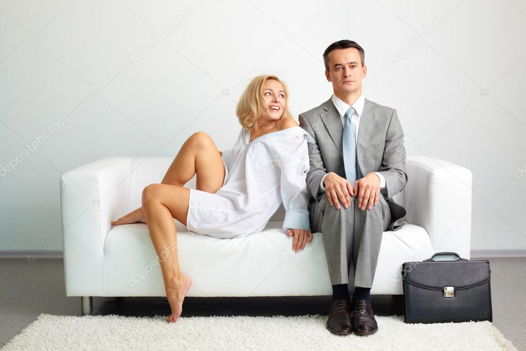 Photo of serious man sitting on sofa with happy seductive woman looking at him — Stock Photo #13724132