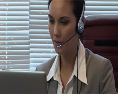 Businesswoman in the office with headset is talking to a partner using IP telephony.