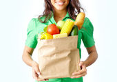 Image of paper packet full of different fruits and vegetables held by female — Stock Photo