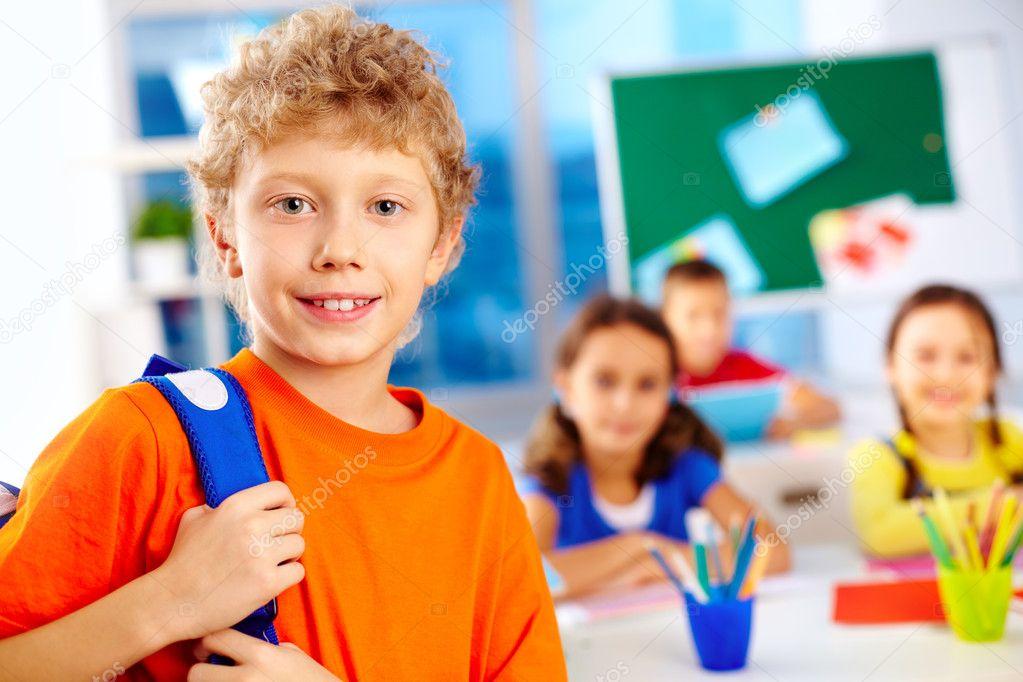 可爱的小学生用背包盯着摄像机与他的同学们的背景的