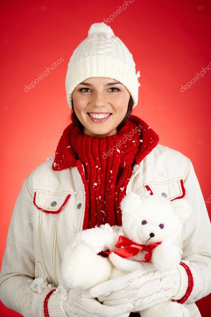 Portrait of happy girl in winterwear holding white teddy bear and looking at camera — Stock Photo #17145109