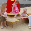 Mothers looking on their daughter playing in sand box — Stock Video