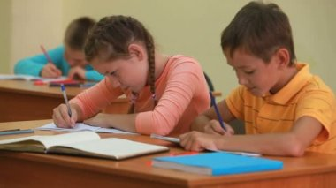 Three little children writing tests in school