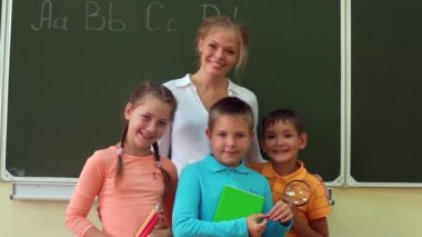 Three pupils and their teacher standing together at blackboard