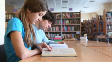 Two teens studying at library