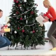 Stock Video: Putting gifts under fir-tree