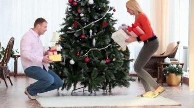 Putting gifts under fir-tree — Stock Video