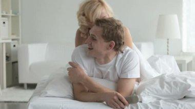 Girl kissing guy in bed — Stock Video