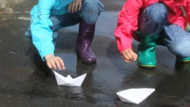 Children playing with paper boats after the rain