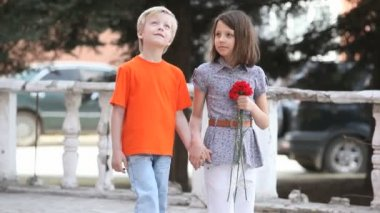 Charming kids walking together holding hands