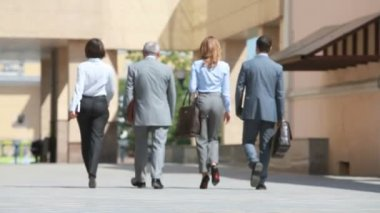 Group of dressed with business elegance walking across the courtyard of the office building