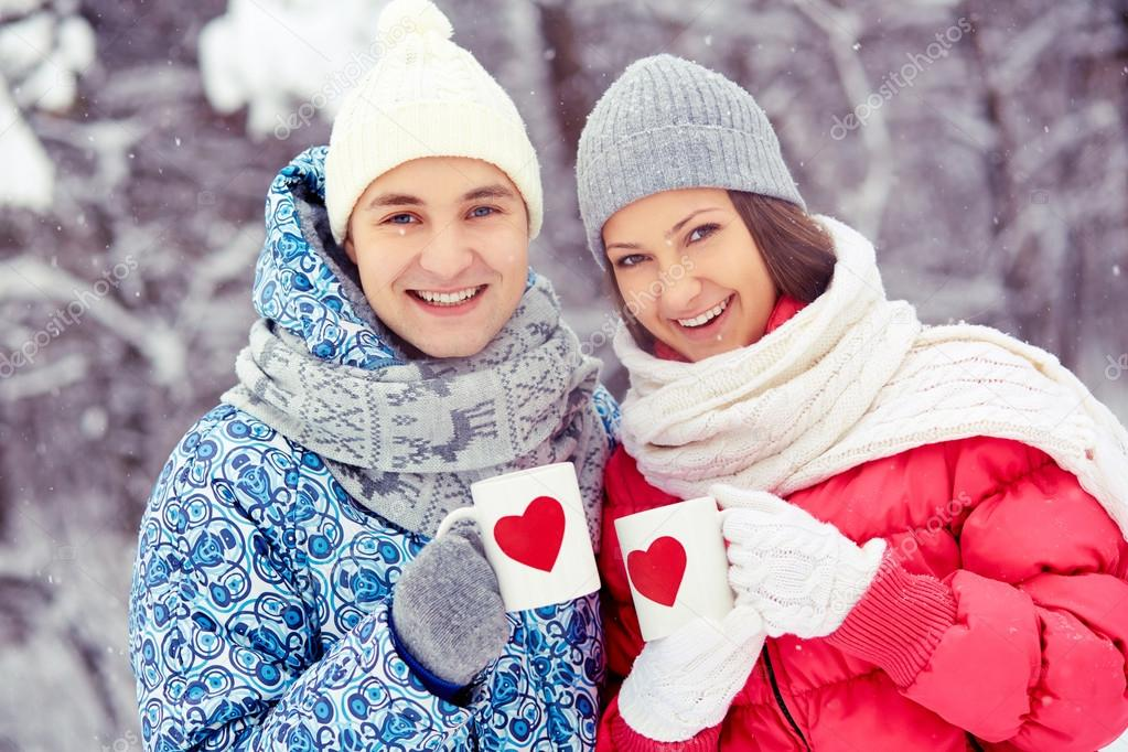 Portrait of happy young couple holding cups with red hearts in winter park  — Stock Photo #19223543