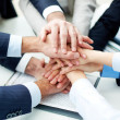 Business partners making pile of hands at meeting — Stock Photo #21186975