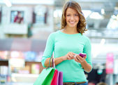 Texting shopper — Stockfoto