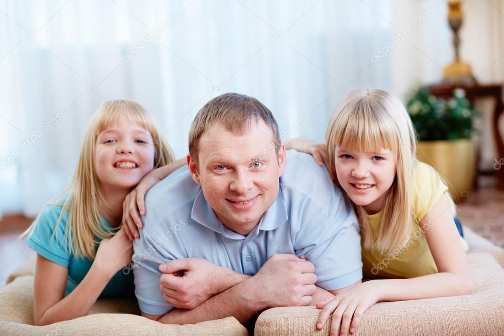 一个英俊的父亲和他可爱的双胞胎女儿的肖像