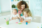 Pretty woman spending time with her children at home — Stock Photo