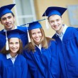 Friends in graduation gowns — Stock Photo