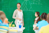 Teacher by blackboard — Stock Photo