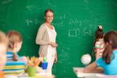 Teacher by blackboard — Stock Photo