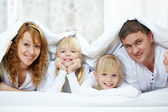 Family under blanket — Stock Photo