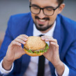 Businessman eating sandwich — Stock Photo
