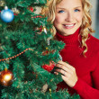 Happy woman looking out of decorated firtree — Stock Photo
