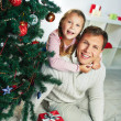 Man with daughter near decorated firtree — Stock Photo