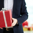 Businessman holding present in red giftbox — Stock Photo