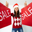 Girl in Santa cap holds  paperbags with symbol of sale — Стоковая фотография