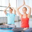 Girl and guy doing exercise for relaxation in gym — Stock Photo