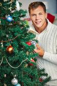 Man by Christmas tree — Stock Photo